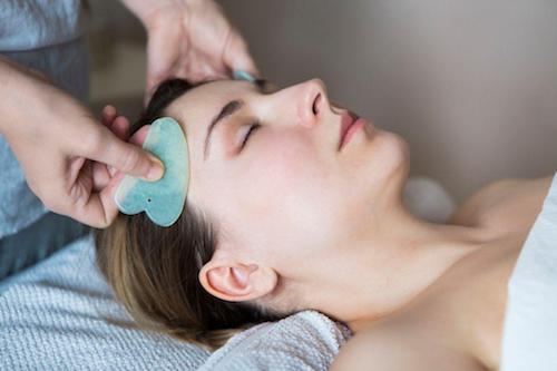 84973875 - young woman have face guasha treatment at asian beauty clinic