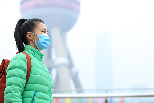 49729627 - worried young woman wear a mask at the pollution city